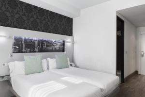 A bed or beds in a room at Petit Palace Plaza Mayor