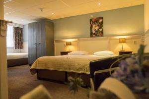 A bed or beds in a room at Hotel de Gulden Leeuw