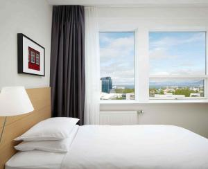 A bed or beds in a room at Hilton Reykjavik Nordica