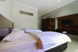 A bed or beds in a room at Aries Biru Hotel & Villa