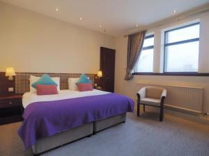 A bed or beds in a room at Caladh Inn