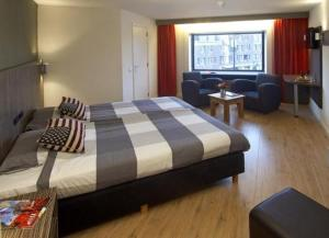 A bed or beds in a room at City Hotel Tilburg
