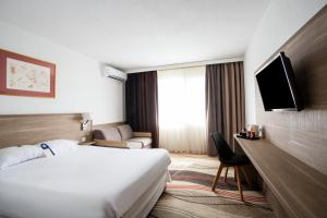 A bed or beds in a room at Golden Tulip Troyes