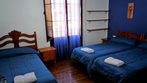 A bed or beds in a room at Pensión Sandoval