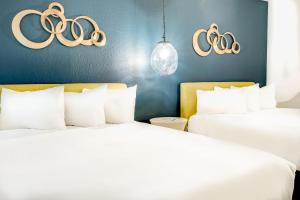 A bed or beds in a room at Downtowner Boutique Hotel
