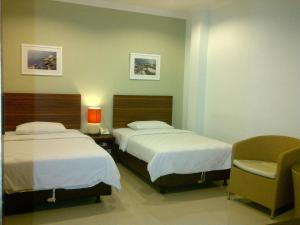 A bed or beds in a room at The Studio Inn Nusa Dua