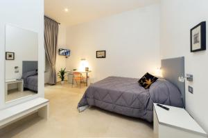 A bed or beds in a room at Il Tesoro Smart Suite & SPA