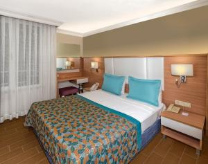 A bed or beds in a room at Royal Garden Beach Hotel