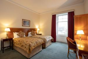 A bed or beds in a room at Grant Arms Hotel