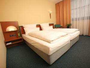 A bed or beds in a room at Transmar Travel Hotel