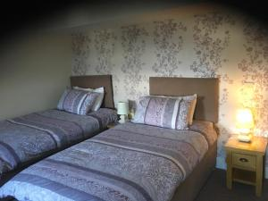 A bed or beds in a room at The Corrie Hotel