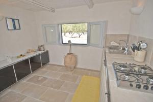A kitchen or kitchenette at TRULLO FALGHERO CON PISCINA PRIVATA