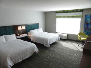 A bed or beds in a room at Hampton Inn By Hilton Paramus