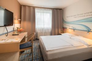 A bed or beds in a room at Plaza Hotel Mühldorf