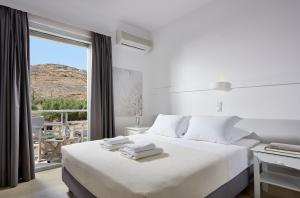 A bed or beds in a room at Kythnos Bay Hotel
