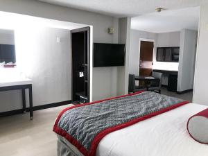 A bed or beds in a room at Ramada by Wyndham Suites Orlando Airport