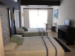 Una televisión o centro de entretenimiento en Hotel Boutique Kinich
