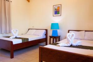 A bed or beds in a room at Blue Lagoon Inn & Suites