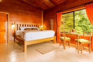 A bed or beds in a room at Arenal Waterfall Lodge