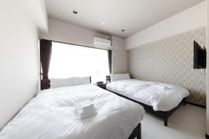TAKUTO STAY OSAKA BENTENCHOにあるベッド