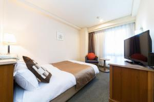 A bed or beds in a room at Pearl Hotel Mizonokuchi