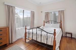 A bed or beds in a room at Busselton River Cottage
