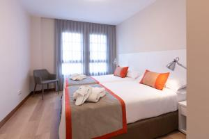 A bed or beds in a room at Aparthotel Los Girasoles