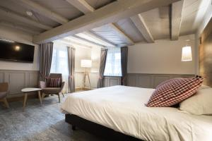 A bed or beds in a room at L'auberge Du Cheval Blanc et Spa