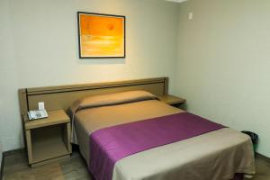 A bed or beds in a room at Corinto Hotel
