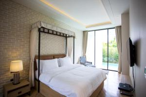 A bed or beds in a room at The Private Pool Villas at Civilai Hill Khao Yai