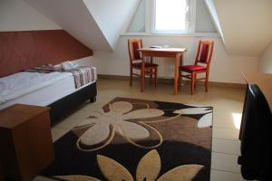 A bed or beds in a room at Auguszta Hotel és Diákszálló