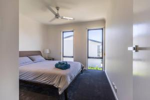 A bed or beds in a room at Homeplus-Escape to Modern Home in Hope Island
