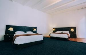 A bed or beds in a room at La Xalca Hotel
