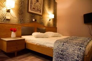 A bed or beds in a room at Eva Hotel Piraeus