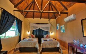 A bed or beds in a room at Island Safari Lodge