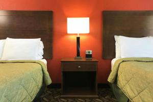 A bed or beds in a room at Rodeway Inn