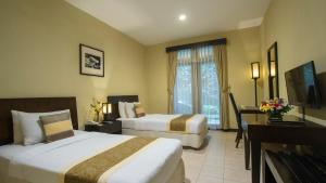 A bed or beds in a room at Puteri Gunung Hotel