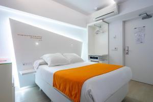 A bed or beds in a room at Atarazanas Málaga Boutique Hotel