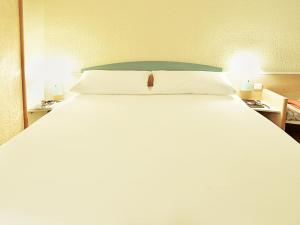 A bed or beds in a room at Hotel ibis Braganca