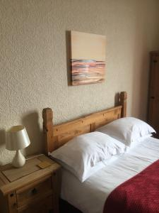 A bed or beds in a room at Camelot Seafront Hotel