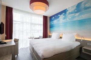 A bed or beds in a room at Ramada The Hague Scheveningen