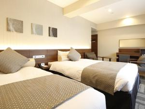 A bed or beds in a room at Hotel Wing International Yokohama Kannai