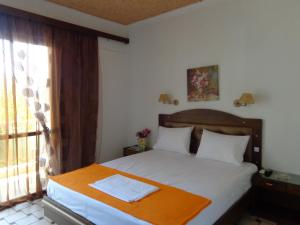 A bed or beds in a room at Angela Hotel