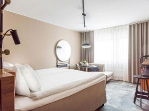 A bed or beds in a room at Clarion Hotel Winn