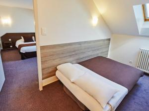 A bed or beds in a room at Campanile Epinal Centre - Gare