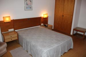 A bed or beds in a room at Hotel Bom Sucesso