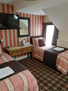 A bed or beds in a room at The Trafford Hotel