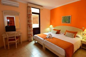 A bed or beds in a room at Villamar Hotel