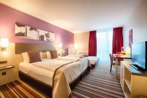 A bed or beds in a room at Leonardo Hotel Hannover Airport