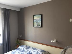 A bed or beds in a room at Hôtel du Sud Vieux Port